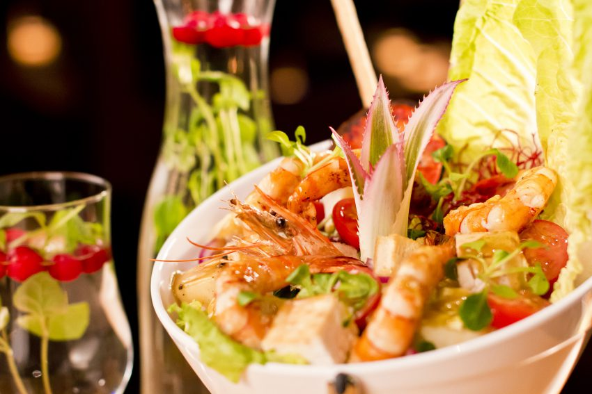 Seafood salad with shrimps in white bowl on black background