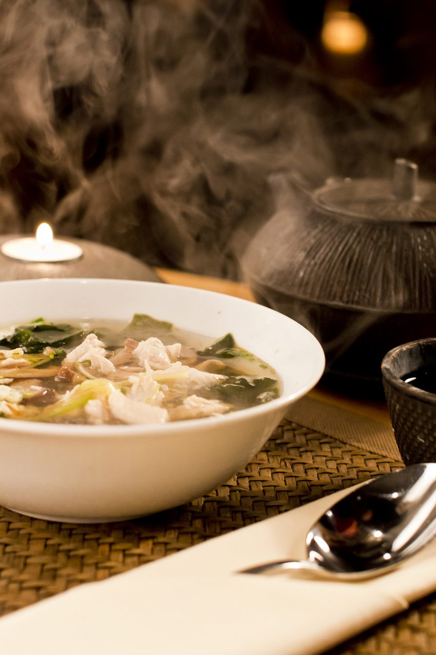 Hot chinese soup with chicken on babmboo matte.